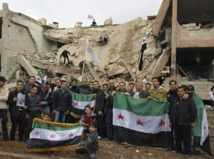 Demonstrators pose with Syrian opposition flags at the site of badly damaged buildings during a protest in Daraya