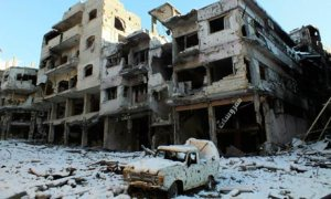 A damaged car and buildings in Homs
