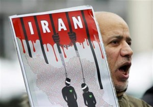 An Iranian exile shouts slogans to protest against executions in Iran during a demonstration in front of the Iranian embassy in Brussels